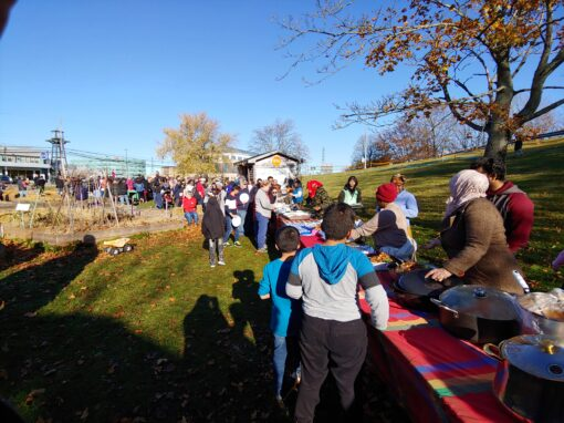line of people receiving food at Common Roots Urban Farm. Outside, and in the sun